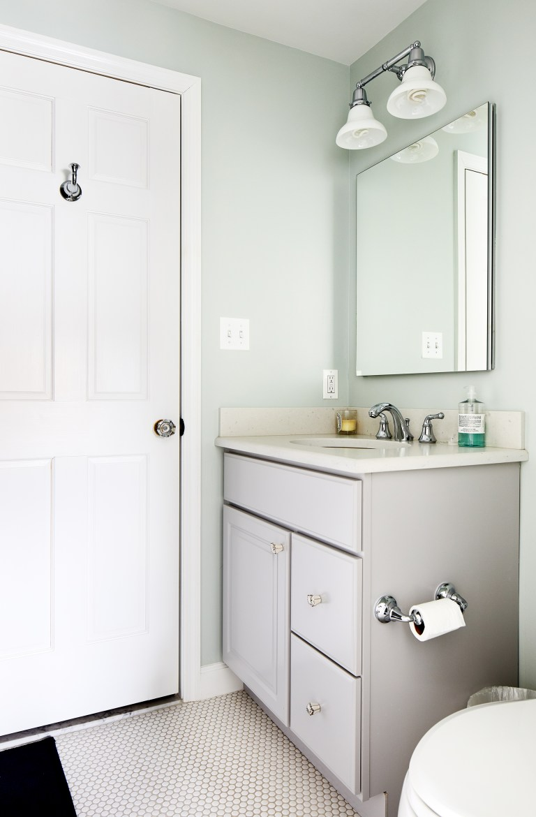 bathroom with soft color palette light green walls white floor vanity with gray cabinetry