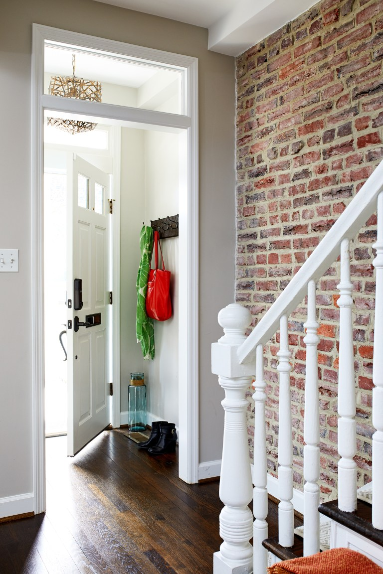 exposed brick wall in entryway along staircase