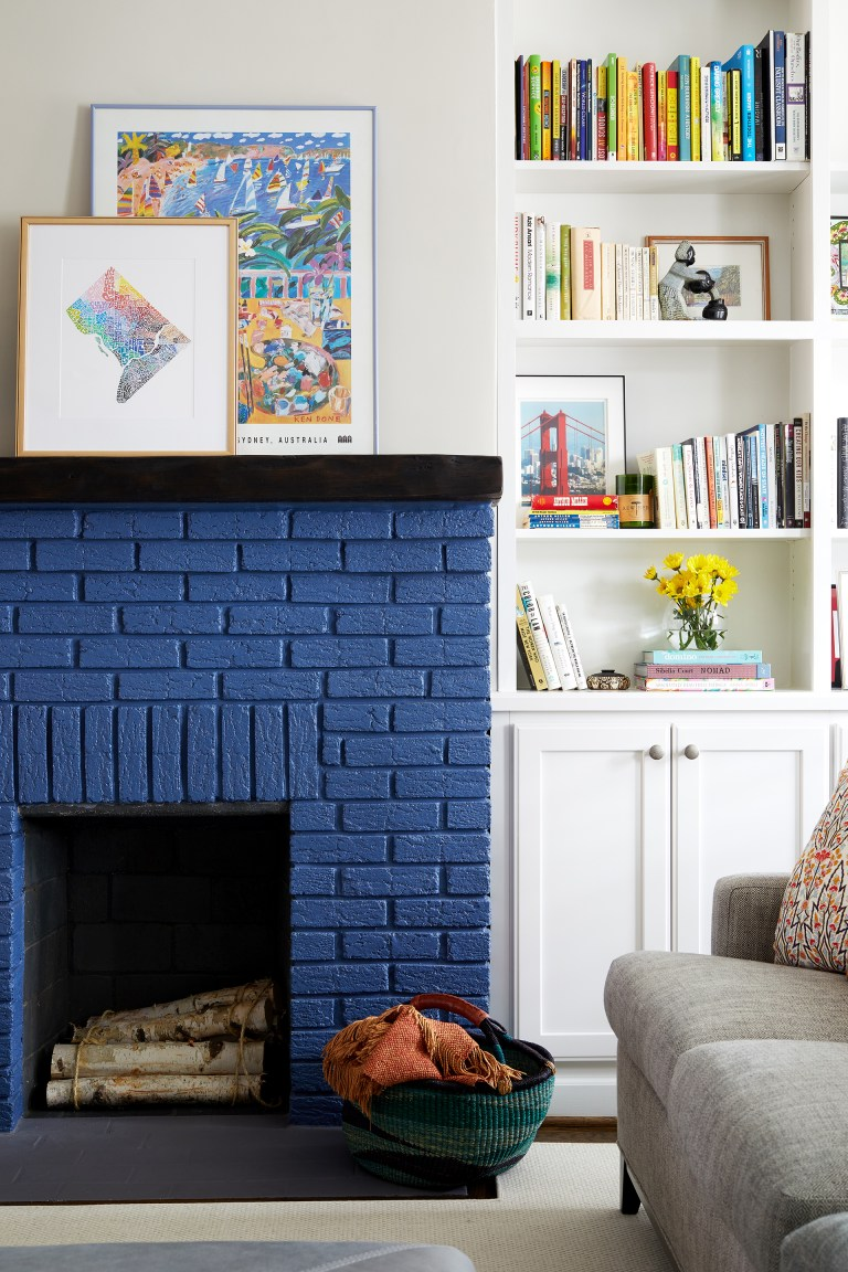 blue painted brick fireplace with dark wood mantle and built in bookcases in living room