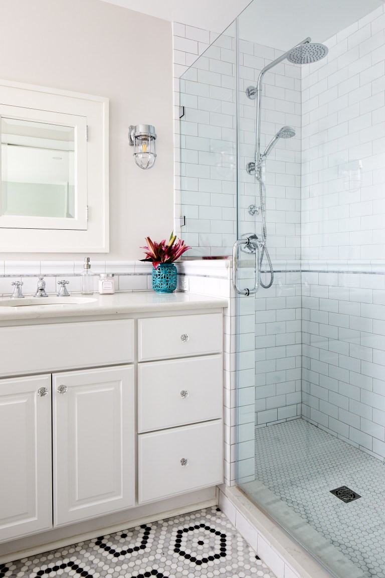 vanity with white cabinetry and sconce lighting shower with white subway tiling and glass door