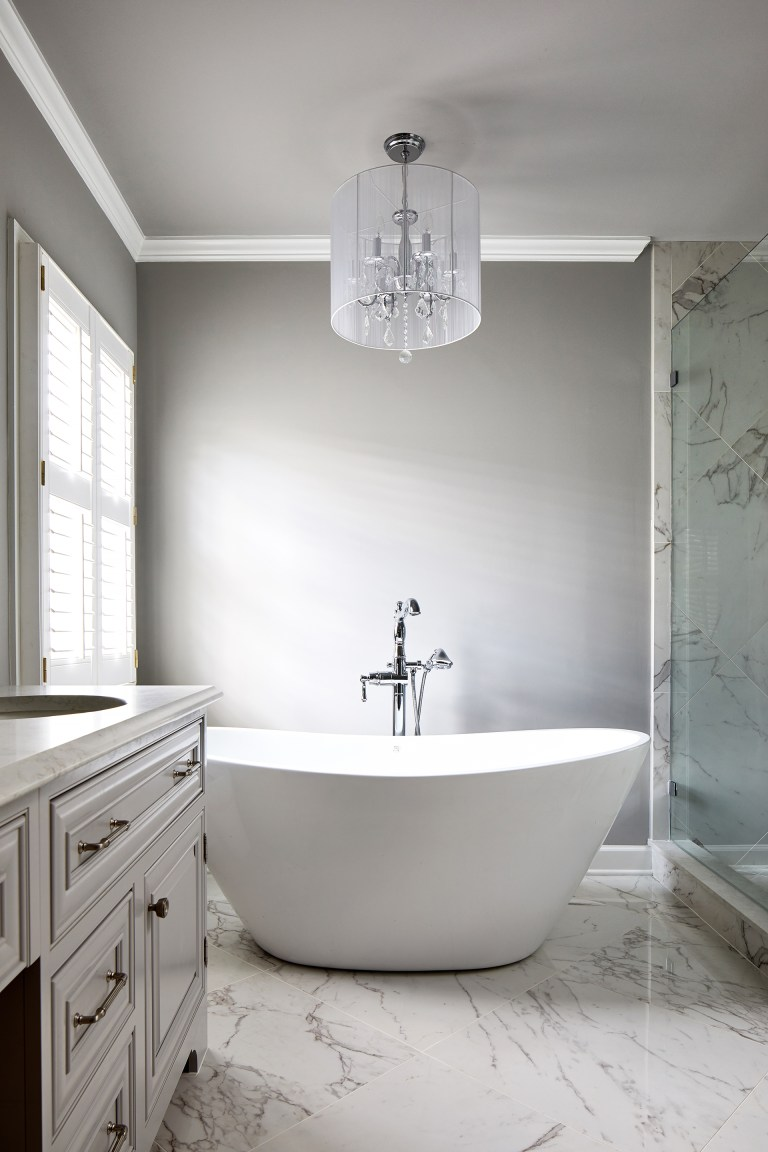 white freestanding one-piece soaking bathtub with center drain and glass light pendant over oval bathtub