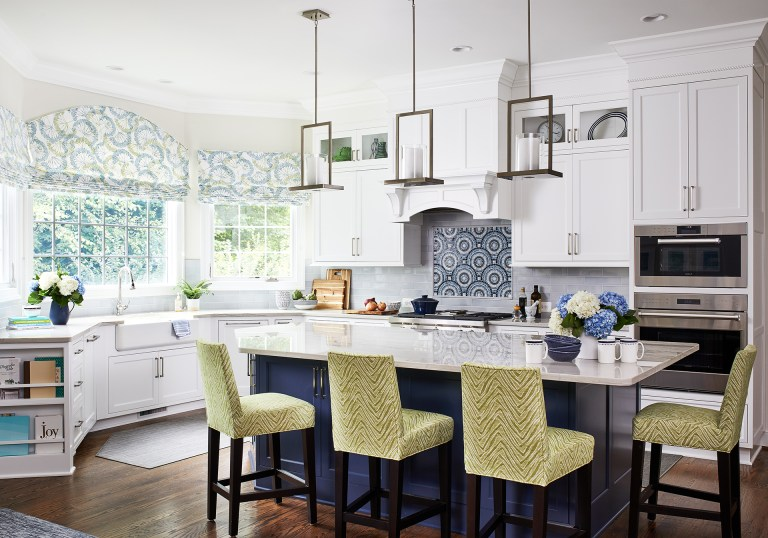 transitional white painted wooden kitchen cabinets with marble granite countertop and white and blue backsplash also triple pendant lamps over kitchen island with seating