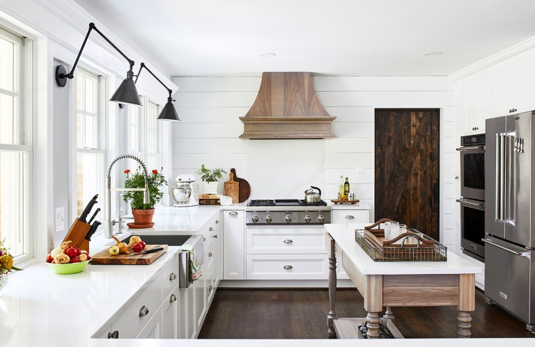 maryland kitchen with two lamps wall light fixtures, farmhouse apron sink, white cabinets and drawers with pull handles. Stainless steel appliances and dark wooden door