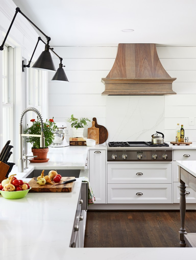 white walls, white cabinets with silver pull handles and wooden dark flooring