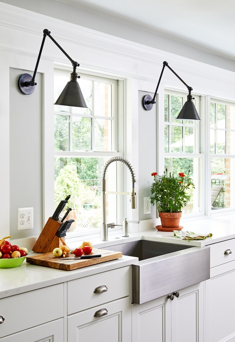 two black pendant lights over kitchen counter and large farmhouse sink