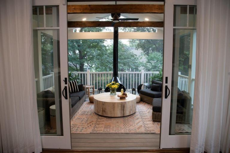 white sliding doors with white curtains, black patio furniture and wooden round table