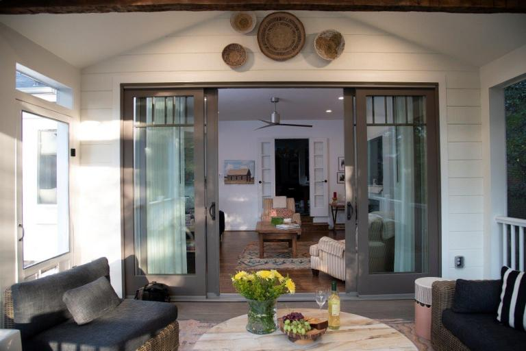 large patio with rusty wood beam, outdoor ceiling fan, wooden round table, black fireplace