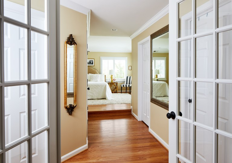 maryland home remodeling with double glass doors leading to master bedroom with light wood flooring and white area rug that matches the window trim and bed covers