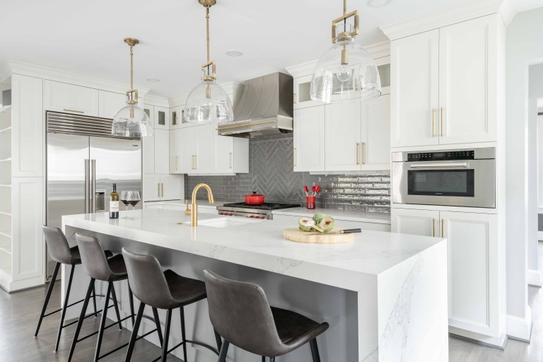 bright kitchen with island floor to ceiling cabinetry stainless steel appliances