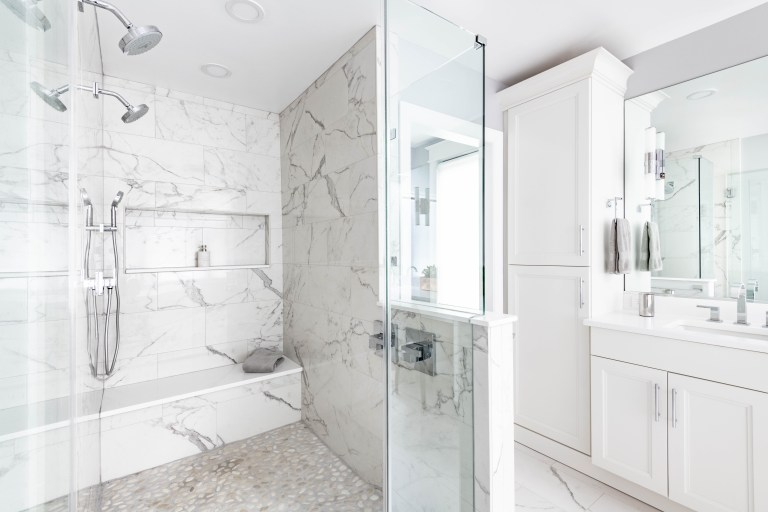 large shower stall with glass door double shower heads and built in storage niche and bench marble tile walls
