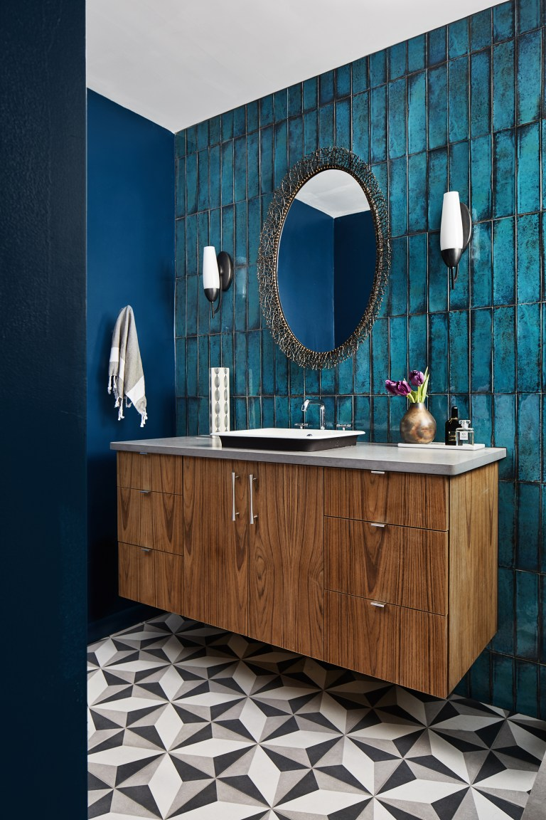 bathroom with geometric tile floors and teal tile feature wall behind floating vanity