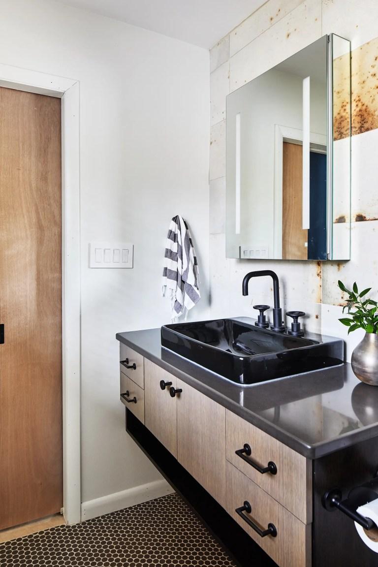 bathroom vanity with black basin sink in industrial style bathroom