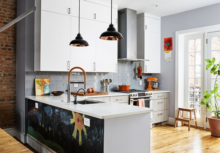 bright dc kitchen with wood floors and glass doors peninsula with chalkboard on back side open to dining room with exposed brick wall