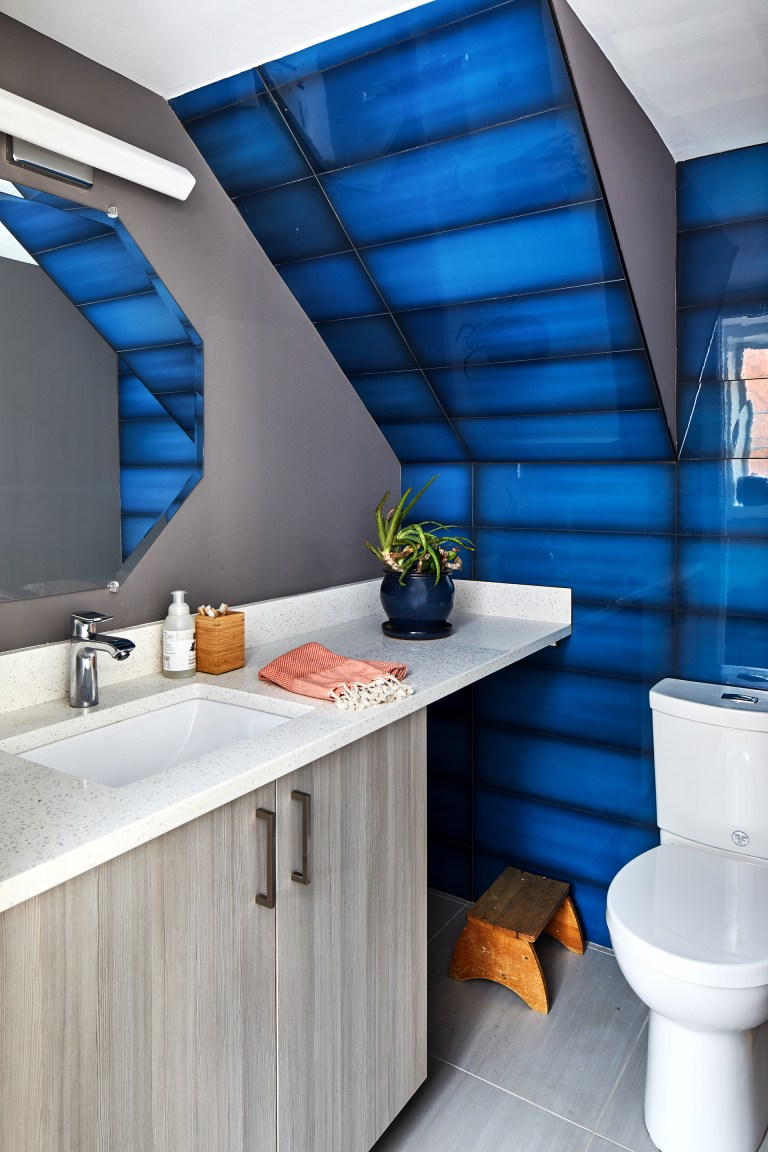 modern renovated bathroom with gray walls and cabinetry white vanity countertops slanted ceiling with blue statement tile