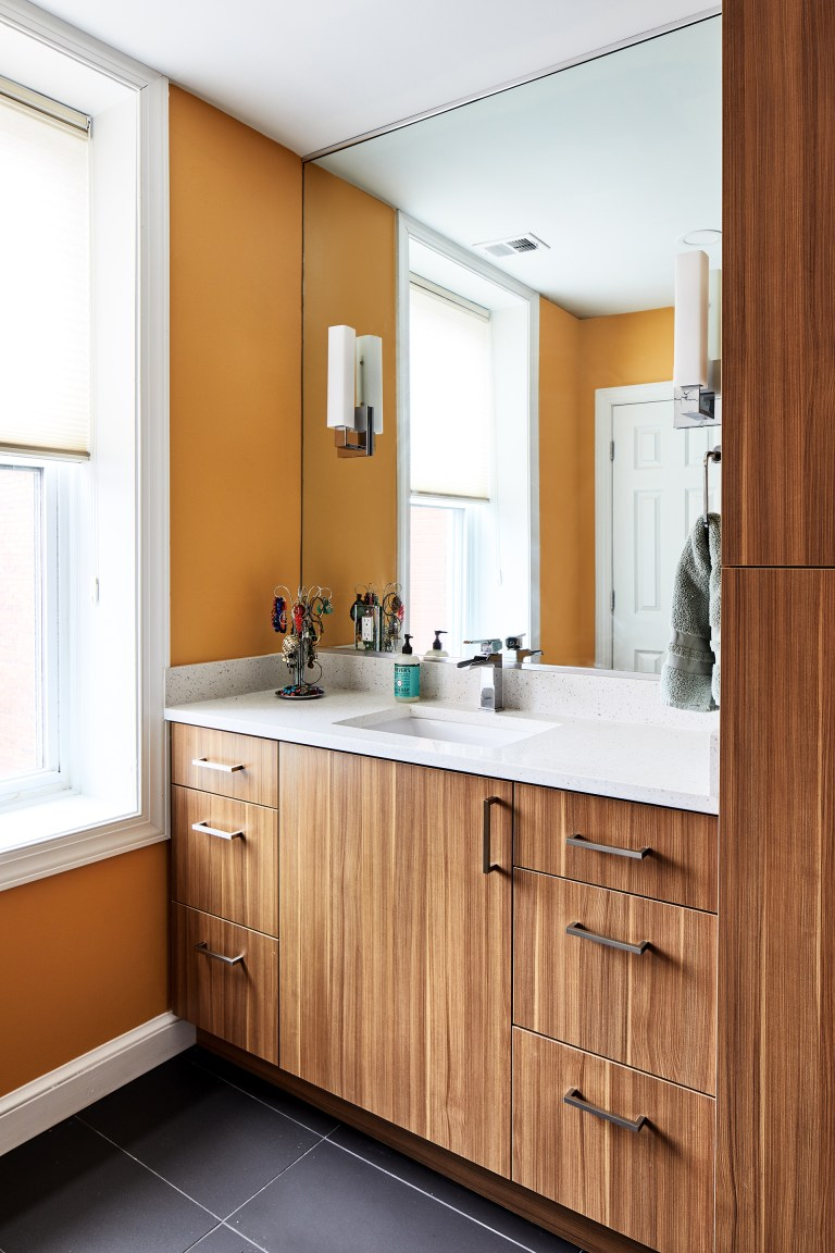 renovated bathroom with natural wood cabinetry orange walls black tile floors plenty of storage
