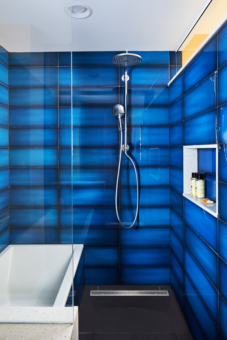 bathtub in shower stall with glass door storage niche and blue tile