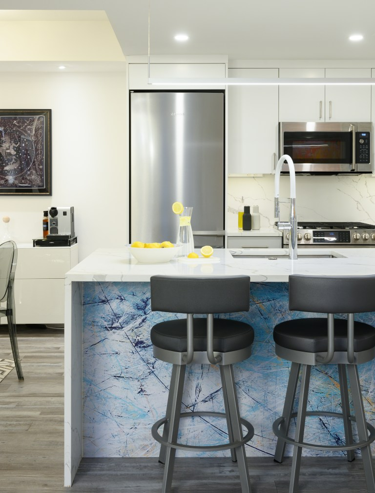marble countertop blue kitchen island facing three chairs
