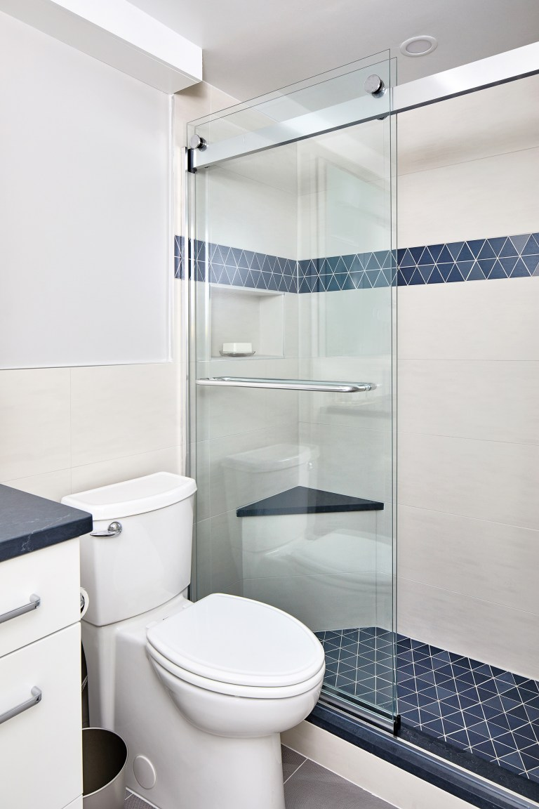 walk-in shower with frameless shower glass door with blue triangle tile on shower floor and middle of the shower wall with a small sitting seat
