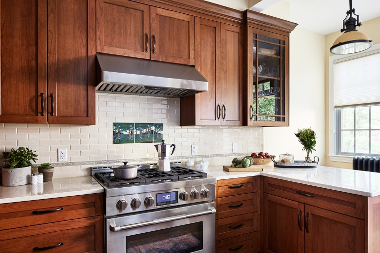 case wood kitchen cabinets, backsplash subway tiles with an inlay tree design