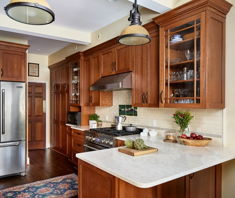 case design kitchen with rich dark wood finish cabinets with pull black handles, corner kitchen island with marble counter and hanging pendant light