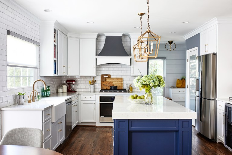 large white top kitchen island with blue draws, two gold glass light pendant, large white cabinets and large farmhouse sink