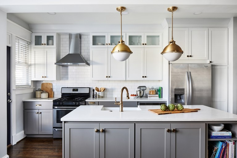 white subway tile featuring light grey wall cabinets with a classic farmhouse sink, white walls and light wood tones balanced and complemented by the hanging pendant lights