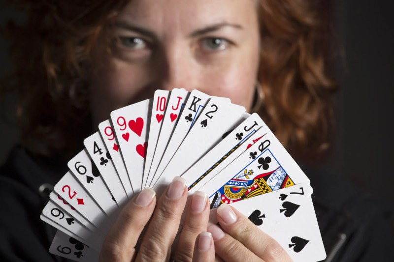 woman holding playing cards in front of her face