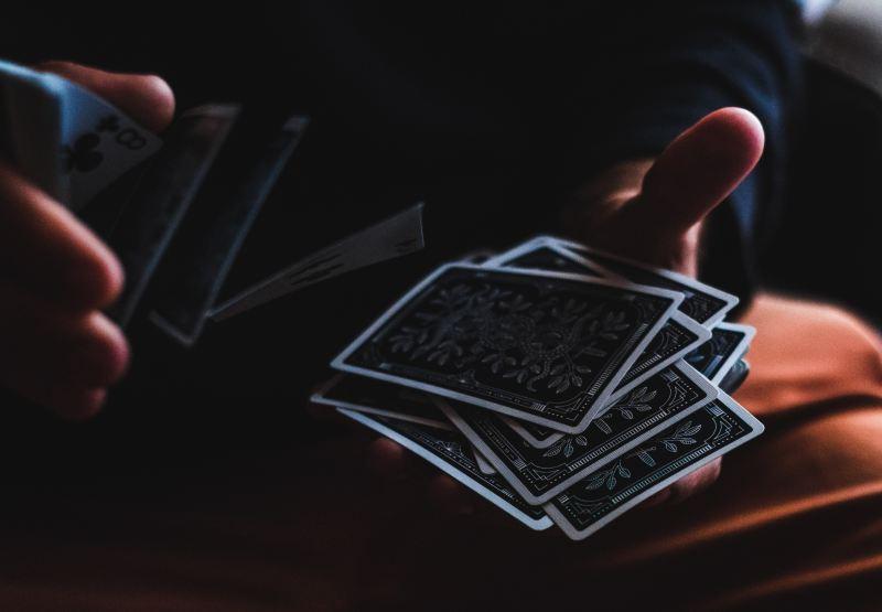man shuffling blackjack playing cards