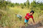 kid picking up rocket in field
