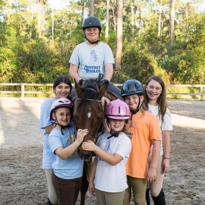 kids posing with horse at horse riding stables