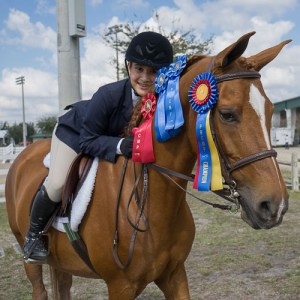young rider posing with Championship ribbons