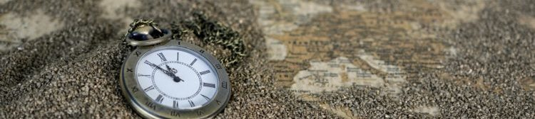 A pocket watch on a map, with grains of sand