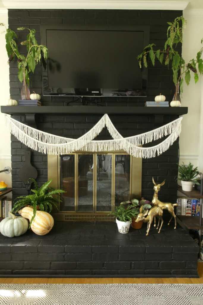 black-and-white-modern-boho-mantel-with-fringe-brass-pumpkins