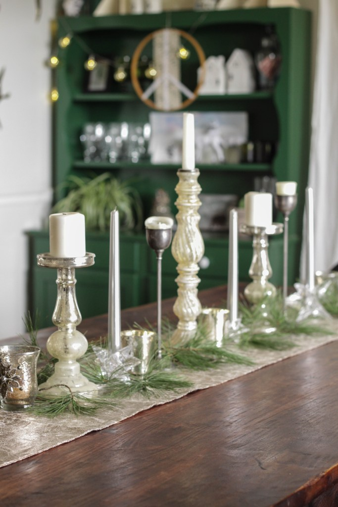 Centerpiece with silver and glass and mercury glass candles and greenery