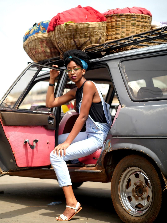 Girl wearing dungarees posing in a cab in tokpa market, cotonou