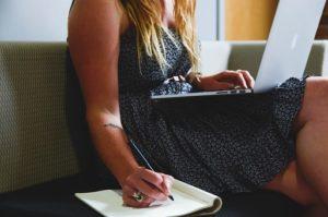 woman writing on book