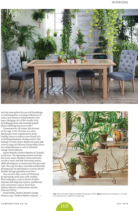 Cambridge Edition Magazine, July 2018. Article on how to Incorporate natural materials into your interior design. Image with many hanging green pants, dining table with grey buttoned fabric chairs. Brown glossy tiled floor.
