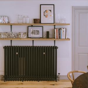 Long cast iron radiator under two wall shelves.