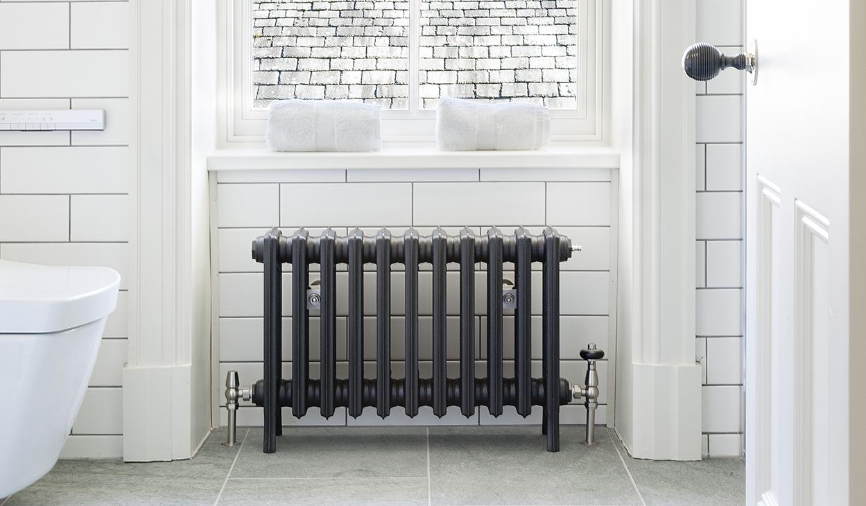 Grey cast iron radiator under window in white bathroom