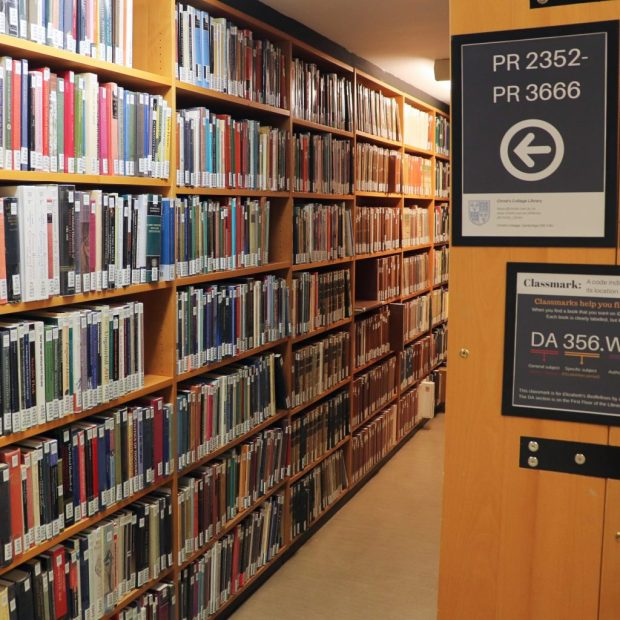 Image of an aisle in a college library. On the left are crowded, colourful books; on the right is the end of a shelf with a poster giving the classmarks of books shelved there.