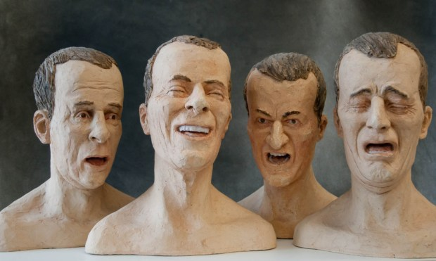 four male heads expressing emotion, the heads may be made of rubber. they look creepy.