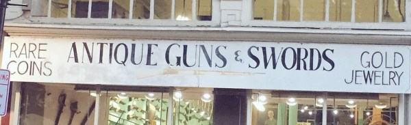 shop sign advertising antique guns, swords... and gold jewelry