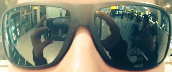 Close up picture of dark wrap around sunglasses, reflected in them is the phone screen and the airport.