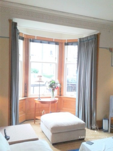 Grey silk interlined curtains in a Fife bay window. Hung on a Silent Gliss track