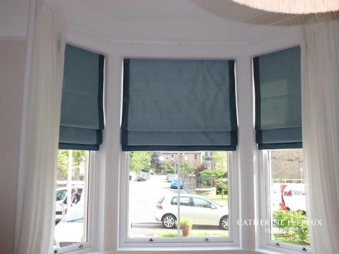 Blue silk roman blinds in an Edwardian Edinburgh bay window.