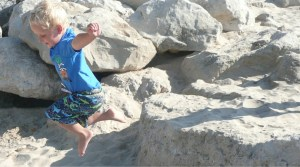 Boy jumping off rocks