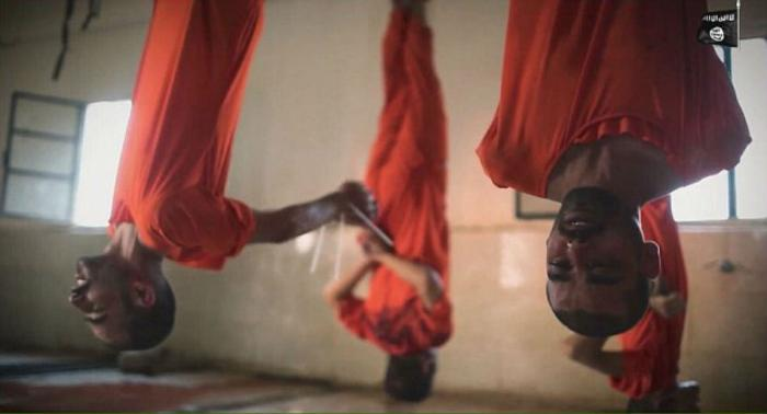 Men hung by their feet from meat hooks.