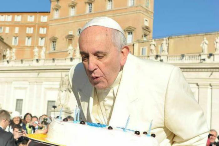 Pope Francis blows out candles on a cake for his 78th birthday.