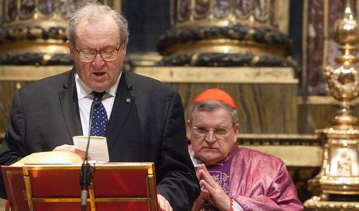 Grand Chancellor Michael Festing reads from the Bible as Cardinal Raymond Burke looks on. Cardinal Burke is Pope Francis