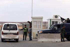 Police officers stand guard at the entrance to the new Azraq Syrian refugee camp, which is under construction east of Amman, Jordan, March 25. Azraq Refugee Camp will open April 30, according to a U.N. official.